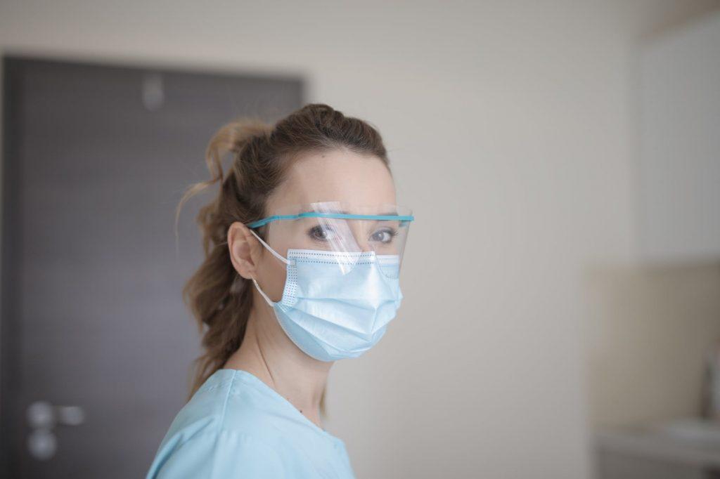 imagem mulher com oculos de protecao transparente e mascara